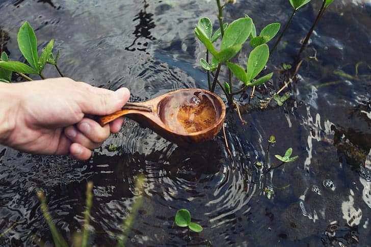 history of baptism wooden spoon in water